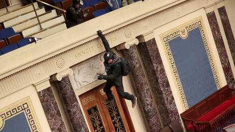 A protester is seen hanging from the balcony in the Senate Chamber on January 6, 2021 in Washington, DC