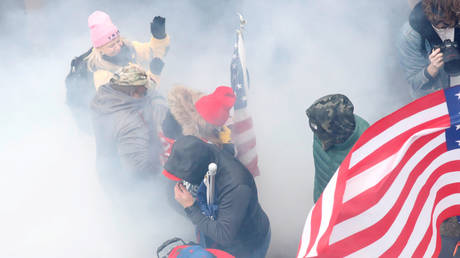 FILE PHOTO: Pro-Trump protesters react amidst a cloud of tear gas during clashes with Capitol police at a rally to contest the certification of the 2020 U.S. presidential election results by the U.S. Congress, at the U.S. Capitol Building in Washington, U.S, January 6, 2021.