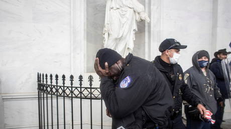 FILE PHOTO: A member of the Capitol police covers his face as pro-Trump protesters storm the US Capitol in Washington, DC, US, January 6, 2021
