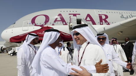 CEO Qatar Airways Akbar Al Baker (R) greets an UAE official after the former finished his tour of the Qatar Airbus A380 at the Dubai Airshow November 8, 2015.