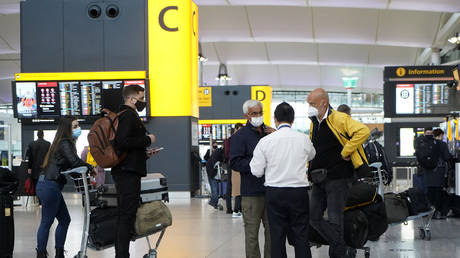 FILE PHOTO Travellers wearing a face mask stand at check-in desks at Terminal 2 of Heathrow Airport in west London on December 21, 2020 © AFP / Niklas HALLE'N