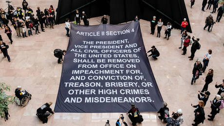 FILE PHOTO: Protesters lay a banner with the Article of Impeachment calling for the removal of President Donald Trump inside of the Hart Senate Office Building during a demonstration on Capitol Hill in Washington, US, January 16, 2020