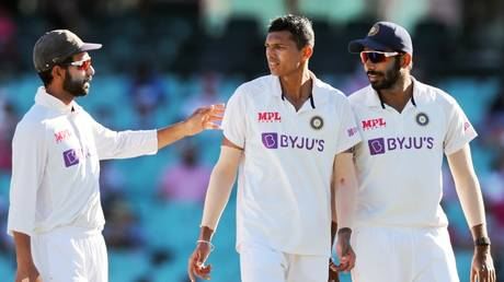 India's captain Ajinkya Rahane (L) speaks with teammates Navdeep Saini (C) and Jasprit Bumrah during the match.