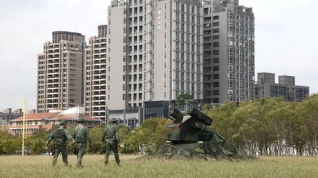 FILE PHOTO: Soldiers walk past a AN/TWQ-1 Avenger mobile air defense missile system during 'Combat Readiness Week' drills in Hsinchu, Taiwan, October 29, 2020