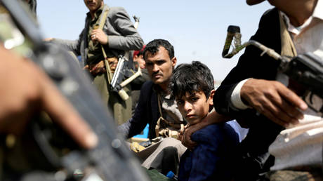 FILE PHOTO: A boy rides with Houthi followers on the back of a patrol truck during the funeral of Houthi fighters killed during recent battles against government forces, in Sanaa, Yemen September 22, 2020.