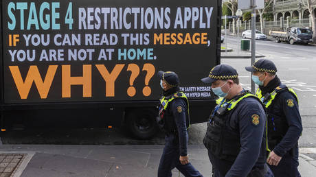 Victorian protective service officers walk past a sign urging people to stay home during Melbourne's lockdown. © AP Photo/Asanka Brendon Ratnayake