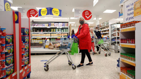 A woman wearing a face mask in a Tesco supermarket, UK