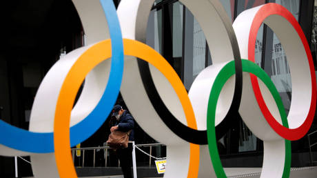 A man wearing a protective mask is seen through the Olympic rings © REUTERS / Issei Kato