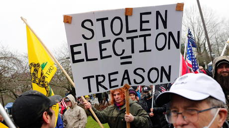 "Cassiopeia Goldenstein, of Ontario, holds a sign saying ""Stolen election = treason"" at a rally in support of U.S. President Donald Trump at the Oregon State Capitol in Salem, Oregon, U.S. January 6, 2021"