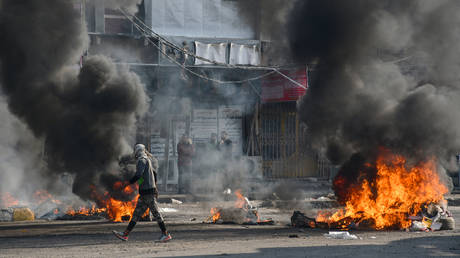 An Iraqi protester walks past burning tyres in the city of Nasiriyah, January 10, 2021