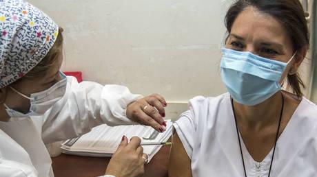 A health worker gets vaccinated with Sputnik V at a hospital in Rosario, Argentina, December 29, 2020. © STR / AFP