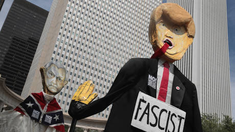 FILE PHOTO: Demonstrators protesting the alt-right movement and mourning the victims of rally in Charlottesville, Virginia carry puppets of President Donald Trump and U.S. Attorney General Jeff Sessionson August 13, 2017 in Chicago, Illinois.
