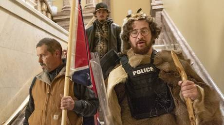 Supporters of President Donald Trump, including Aaron Mostofsky, right, who is identified in his arrest warrant, walk down the stairs outside the Senate Chamber in the U.S. Capitol, in Washington.