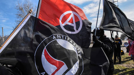 FILE PHOTO: Members of Antifa fly flags during a protest against the Alt-right outside a hotel in Warren, Michigan.