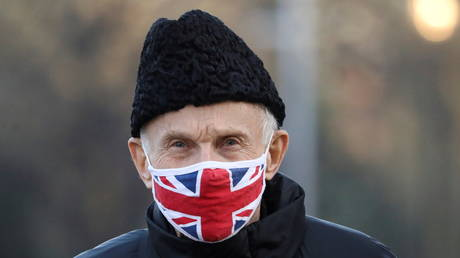 A man wears a Union Jack flag face mask, amid the spread of the coronavirus disease, outside Kensington Palace Gardens in London,