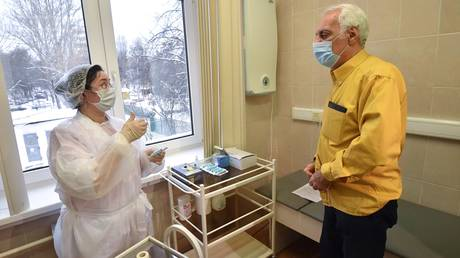 A medical worker examines an elderly patient before vaccination against the COVID-19 coronavirus with the Sputnik V vaccine at the vaccination center of the city polyclinic No. 2 in North Chertanovo.
