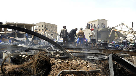 Workers clear the debris at a warehouse after it was reportedly hit by a Saudi airstrike, in Sanaa, Yemen, July 2020. © Mohammed Huwais / AFP