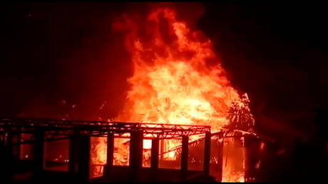 A building burns during a fire outbreak in Rohingya refugee camp, in Cox's Bazar, Bangladesh January 14, 2021 in this still image obtained from a video.