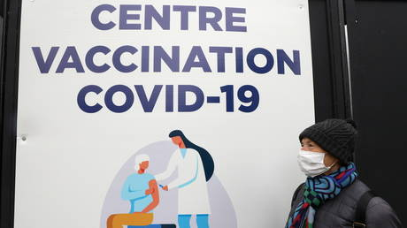 FILE PHOTO: A woman, wearing a protective face mask, walks past a COVID-19 vaccination center in Nice, France. © REUTERS / Eric Gaillard