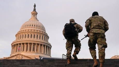 National Guard members walk at the Capitol, in Washington, January 15, 2021