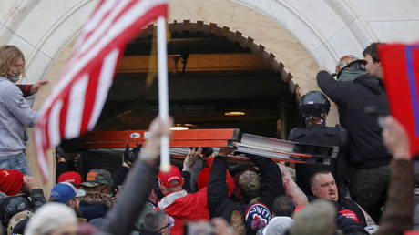 A mob of supporters of U.S. President Donald Trump attempt to use a ladder on a group of law enforcement personnel as they storm the U.S. Capitol Building in Washington, U.S., January 6, 2021. © REUTERS/Leah Millis