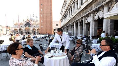 FILE PHOTO: A waiter serves customers at a restaurant on St. Mark's Square in Venice, June 12, 2020 © AFP / Andrea Pattaro