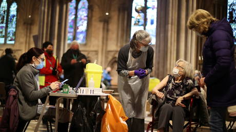 A woman receives a Covid-19 vaccine inside Lichfield Cathedral in Birmingham, UK. © REUTERS/Carl Recine