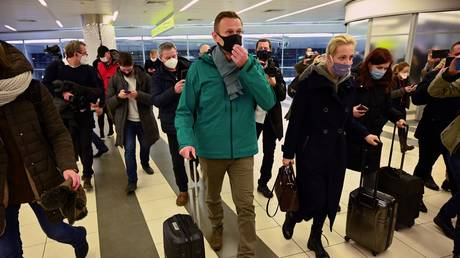 Russian opposition leader Alexei Navalny and his wife Yulia walk towards the passport control point at Moscow's Sheremetyevo airport upon the arrival from Berlin on January 17, 2021 © AFP / Kirill KUDRYAVTSEV