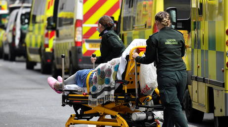 FILE PHOTO: Medical workers bring a patient out of an ambulance, amid the coronavirus pandemic, outside Royal London Hospital, in London, Britain.