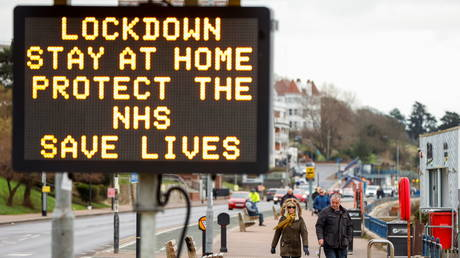 A man and woman walk along the seafront as a government sign displays a COVID-19 warning amid the coronavirus disease outbreak, in Southend-On-Sea, Britain January 11, 2021. © REUTERS/John Sibley