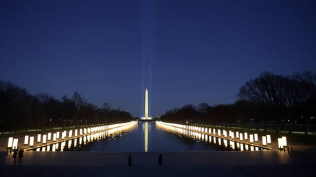 The Reflecting Pool is lighted as a Covid-19 Memorial in front of the Washington Monument in Washington, DC, on January 19, 2021