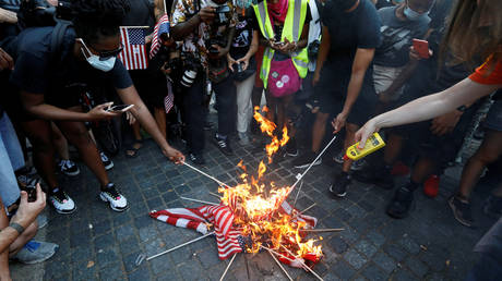 FILE PHOTO: Demonstrators burn U.S. flags during a Black Lives Matter protest on the Fourth of July Holiday in Manhattan, New York City, U.S., July 4, 2020