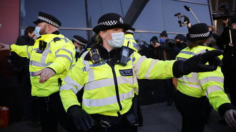 Police officers ask media and onlookers to get back as they detain an anti-lockdown protester in Clapham, south London, on January 9, 2021 as life continues in Britain's third lockdown that prohibits large public gatherings in an effort to control surging cases of Covid-19.