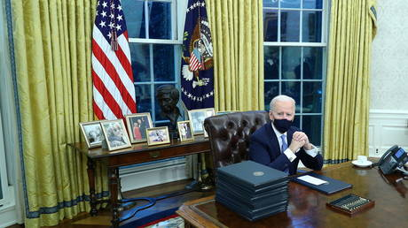 US President Joe Biden signs executive orders inside the Oval Office at the White House in Washington, US, January 20, 2021