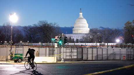 A cyclist passes the U.S Capitol secured with additional fencing and barriers before sunrise on President-elect Joe Biden's Inauguration Day in Washington, U.S., January 20, 2021.
