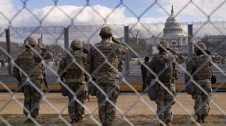 National Guard members salute in front of the US Capitol building during the inauguration of President Joe Biden, January 20, 2021.