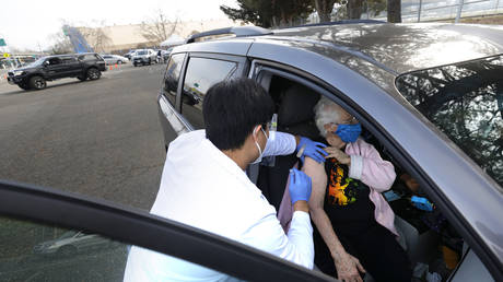 A medical worker administers a Moderna vaccine at a drive-thru Covid-19 clinic in Santa Rosa, California, January 13, 2021. © Justin Sullivan / Getty Images North America