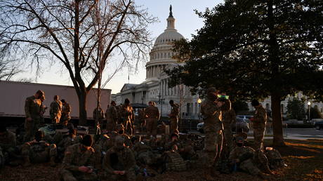 National Guard troops rest on a yard in front of the US Capitol