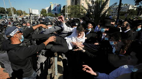 Policemen remove an Ultra-Orthodox Jew during a protest in Ashdod, Israel. © Reuters / Amir Cohen