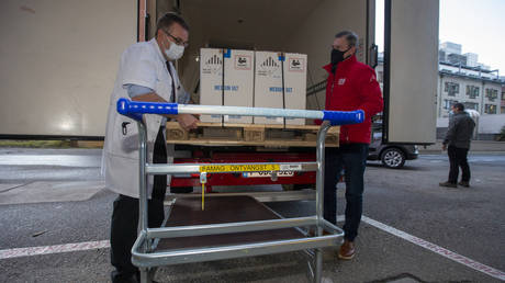 FILE PHOTO: A medical staff member receives the first Pfizer-BioNTech Covid-19 disease vaccine delivery at the UZ Leuven hospital, Leuven, on December 26, 2020 as begins a vaccination programme in EU countries.