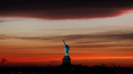 FILE PHOTO: The sun sets behind the Statue of Liberty after a rain storm in New York, U.S., May 15, 2018