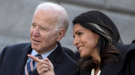 Tulsi Gabbard is shown speaking with Joe Biden when both were Democrat presidential candidates in January 2020.