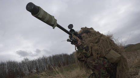 FILE PHOTO: A camouflaged British infantry soldier is seen looking down the telescopic sight of the British-made Long Range L115A3 sniper rifle on Salisbury Plain, Warminster, England