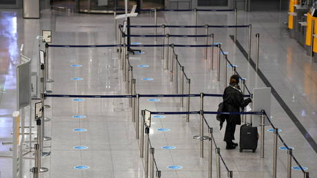 A single passenger stands in a line in front of a check-in counter at Franz-Josef-Strauss airport in Munich, Germany, November 12, 2020.
