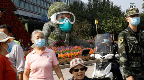 FILE PHOTO. People walk past a floral installation featuring a medical worker on Changan Avenue in Beijing. ©REUTERS / Tingshu Wang