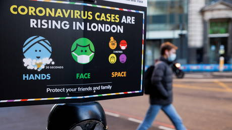 A man wearing a face mask walks past a government sign with instructions about COVID-19 amid the coronavirus disease (COVID-19) outbreak, in London, Britain, January 25, 2021.