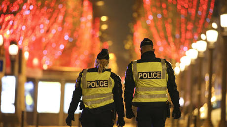 FILE PHOTO: Police officers patrol a street during a curfew in Paris, France, December 2020. © Stefano Rellandini / AFP