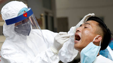 A medical specialist collects a swab sample at a Covid-19 testing center in Hanoi, Vietnam August 10, 2020