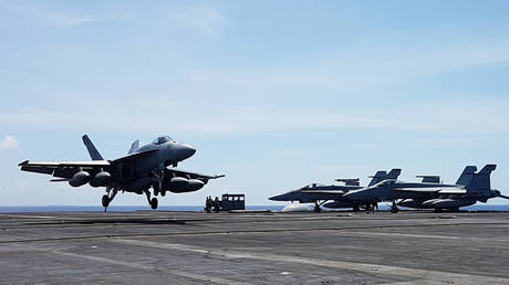 FILE PHOTO: An F-18 fighter, on patrol, lands on the deck of the USS Theodore Roosevelt, transiting the South China Sea April 10, 2018