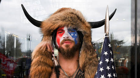 """FILE PHOTO: Jacob Chansley, the """"QAnon Shaman,"""" is seen in face paint as supporters of then-US president Donald Trump gathered for a rally in Washington, DC, January 6, 2021."""